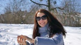 Den aktiva le kvinnan i mörk solglasögon spelar kastar snöboll på bakgrund för blå himmel i parkerar under solig dag arkivfilmer