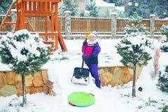Den aktiva lyckliga flickan bygger is och snökullen med skyffeln Arkivfoto