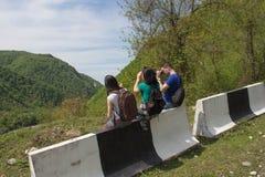 Den aktiva och sunda livsstilen på sommarsemester och helg turnerar Turister som hitching en ritt Fotografering för Bildbyråer