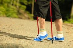Den aktiva pensionären lägger benen på ryggen i nordiskt gå för gymnastikskor i en parkera Royaltyfri Fotografi