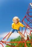 Den aktiva pojken står på rött rep med ben ifrån varandra Arkivfoto