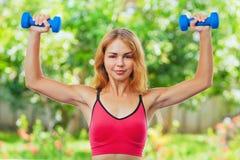 Den aktiva sportiga kvinnan som gör morgon, övar med hemmastadda hantlar Royaltyfri Bild