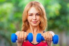 Den aktiva sportiga kvinnan som gör morgon, övar med hemmastadda hantlar Arkivbilder