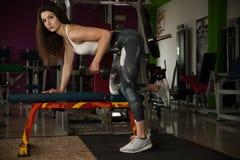 Den aktiva unga kvinnan utarbetar hennes armar i idrottshall för konditionklubba royaltyfri bild
