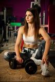 Den aktiva unga kvinnan vilar efter genomkörare i idrottshall för konditionklubba royaltyfria bilder