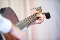 den akustiska detaljgitarrgitarristen hands instrumant musikaliskt leka för aktör royaltyfria foton