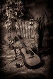 Den akustiska gitarren och tömmer stol i svartvitt Royaltyfri Bild
