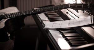 Den akustiska gitarren står på pianot med anmärkningar, närbilden, härlig färgbakgrund royaltyfria bilder