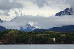Den alaskabo fyren på sida av berg fördunklar att driva in Royaltyfria Bilder