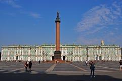 Den Alexandria kolonnen och eremitboningen på slotten kvadrerar i St Petersburg Arkivfoto