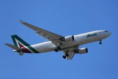 Den Alitalia flygbussen A330 stiger ned för att landa på den internationella flygplatsen för JFK i New York Royaltyfri Foto