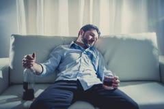 Den alkoholiserade affärsmannen i blått lossar att sova för band som drickas med whiskyflaskan på soffan Arkivbilder