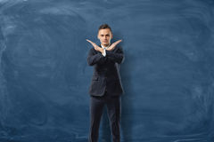 Den allvarliga affärsmannen gör ett stopptecken med hans händer på blå svart tavlabakgrund Fotografering för Bildbyråer