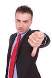 Den allvarliga affärsmannen som visar tummen gör en gest ner Arkivbild