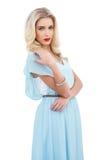 Den allvarliga blonda modellen i blått klär att posera rymma hennes skuldra Arkivbild