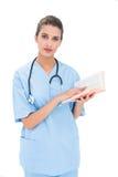 Den allvarliga bruna haired sjuksköterskan i blått skurar att rymma en bok arkivfoto