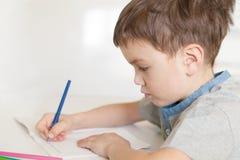 Den allvarliga eftertänksamma eleven sitter på skrivbordet Arkivfoto