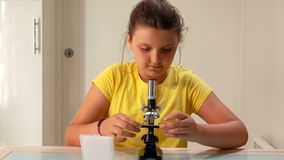 Den allvarliga flickan ändrar en prövkopia i ett mikroskop stock video