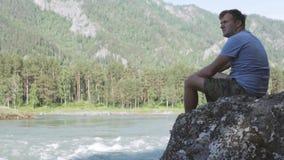 Den allvarliga fundersamma mannen ser en bergflod lager videofilmer