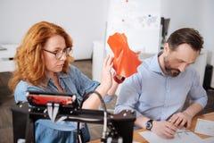 Den allvarliga härliga kvinnan som rymmer en 3d, skrivev ut objekt Fotografering för Bildbyråer