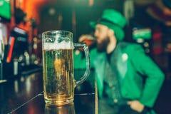 Den allvarliga koncentrerade unga mannen i Sts Patrick dräkt sitter på stångräknaren i bar bara Råna av ölställning framme av hon royaltyfri fotografi