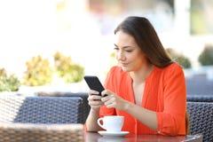 Den allvarliga kvinnan anv?nder en smart telefon i en coffee shop royaltyfria foton