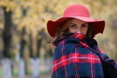 Den allvarliga kvinnan i röd hatt i höst parkerar Royaltyfri Foto
