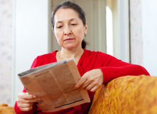Den allvarliga kvinnan ser tidningen Royaltyfri Foto