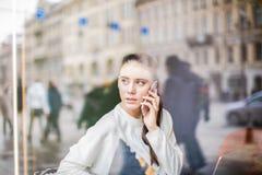 Den allvarliga kvinnliga entreprenören som har celltelefonkonversation under, vilar i coffee shop royaltyfri foto