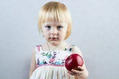 Den allvarliga lilla flickan rymmer ett rött äpple Royaltyfria Foton