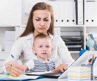 Den allvarliga mamman med barnet är Ñ- som arbetar oncentratedly bak bärbara datorn royaltyfria foton