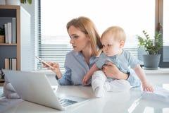Den allvarliga mamman som arbetar på kontoret med, behandla som ett barn royaltyfria foton