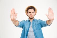 Den allvarliga mannen i blått skjorta- och hattvisningstopp gör en gest Royaltyfria Bilder