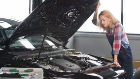Den allvarliga mekanikerkvinnan som arbetar på hennes egen reparation, shoppar stock video