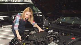 Den allvarliga mekanikerkvinnan som arbetar på hennes egen reparation, shoppar arkivfilmer