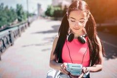 Den allvarliga och fundersamma flickan är den stående yttersidan på gatan och att se på hennes musikspelare Hon bär exponeringsgl Royaltyfri Fotografi