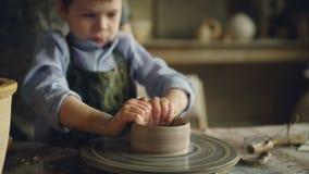 Den allvarliga pojken bildar krukan från lera på att kasta hjulet, medan delta i krukmakerigrupp i mitt för barn` s intressera arkivfilmer