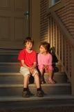 Den allvarliga pojken och flickan sitter på trappa nära dörr Royaltyfri Bild