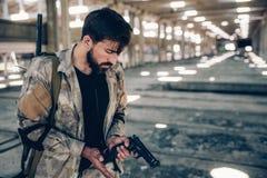 Den allvarliga professionelln laddar upp hans vapen Han rymmer hans assistent på den låga kanten av pistolen Grabben ser det Arkivbild