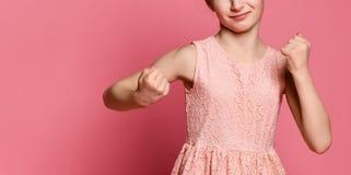 Den allvarliga rödhåriga flickan försvarar hennes nävar med boxats Uttryck av sinnesrörelse- och känslabegreppet royaltyfria bilder