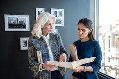 Den allvarliga stilfulla åldriga kvinnlign står med hennes anställd Arkivbild