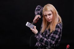 Den allvarliga unga flickan klämmer en bruten smartphone med ett konstruktionsgem Svart bakgrund Arkivbilder