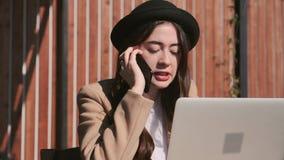 Den allvarliga unga kvinnan diskuterar vid mobiltelefonen och använder bärbara datorn på gatan arkivfilmer