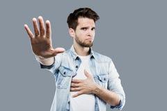 Den allvarliga unga mannen gör stoppet att göra en gest med gömma i handflatan över grå bakgrund Fotografering för Bildbyråer