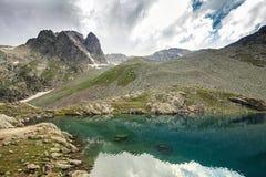 Den alpina sjön bland vaggar Arkivbilder