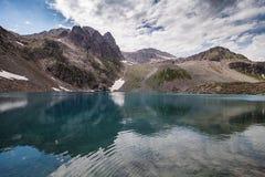 Den alpina sjön bland vaggar Arkivfoto
