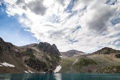 Den alpina sjön bland vaggar Arkivfoton