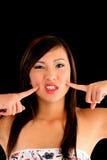 den amerikanska asiatet varar fräck mot fingrar som är teen till kvinnan Royaltyfria Bilder