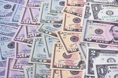 Den amerikanska dollaren av olika valörer blured bakgrund arkivbilder