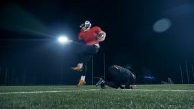 Den amerikanska fotbollsspelaren hoppar över en annan spelare, medan konkurrera på ett tomt fält arkivfilmer